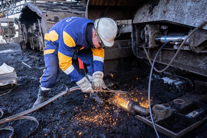 Beim Eimerkettenbagger muss eine Fahrwerkspindel ausgetauscht werden. Schweißerhose, Sicherheitshandschuhe und Schutzbrille sind bei dieser Arbeit obligatorisch. Foto: Thomas Bär